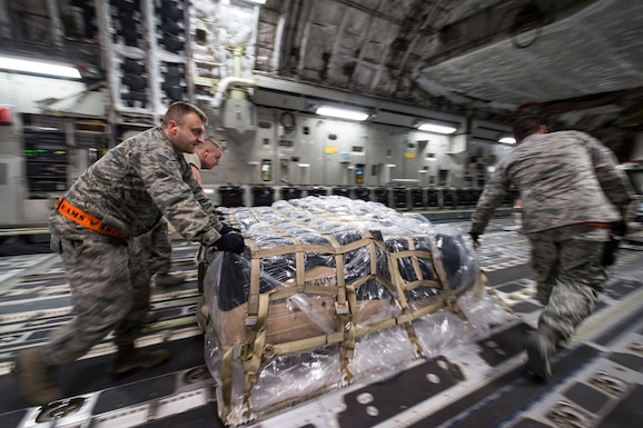 U.S. Air Force Airmen from the 8th Expeditionary Air Mobility Squadron load cargo onto a C-17 Globemaster III at Al Udeid Air Base, Qatar, in support of Operation Resolute Support, Jan. 13, 2016. Operation Resolute Support is the evolution from the International Security Assistance Force (ISAF) combat mission to Train, Advise and Assist mission of Afghanistan. (U.S. Air Force photo by Staff Sgt. Corey Hook/Released)