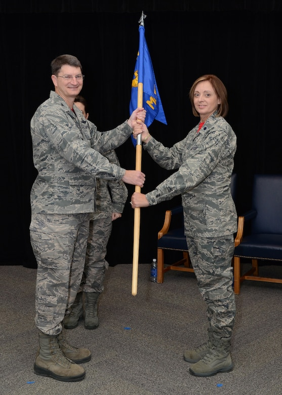"""Lt. Col. Patti Fries receives the 131st Medical Group guidon from Col Mike Francis, 131st Bomb Wing Commander, during the assumption of command ceremony at Whiteman Air Force Base, Missouri, Jan 10. """"You deserve nothing less than my best, and I'll give it to you, that is my promise,"""" said Fries. (U.S. Air National Guard photo by Staff Sgt. Brittany Cannon)"""