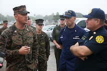 Marine Capt. Shane Vickers, the officer in charge of Marine Wing Support Detachment 24, and a Martin, Tenn., native, speaks with Battalion Chief Paul Stankiewicz, the battalion chief of the Honolulu Fire Department and an Aiea, Hawaii, resident, along with other members of the search and rescue operation at Haleiwa Beach Park, Jan. 15, 2016. Members of the search and rescue operation have been working continuously in order to locate the missing personnel and downed aircraft.
