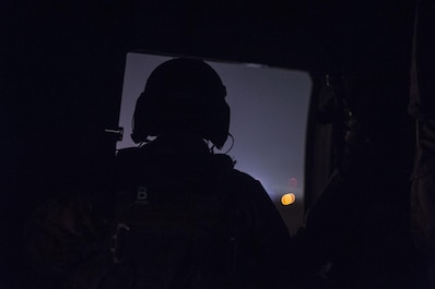 A flight engineer looks out the open door of an Afghan Air Force Mi-17 helicopter during a night flight at Hamid Karzai International Airport, Kabul, Afghanistan, December 2015. (U.S. Air Force photo by Staff Sgt. Corey Hook/Released)