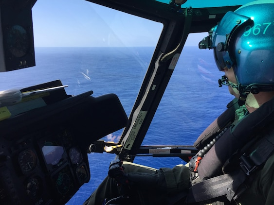 The crew of a Coast Guard MH-65 Dolphin helicopter  (CG 6608) from Air Station Barbers Point conducts a search for 12 Marine aviators off the North Shore of Oahu Jan. 17, 2016. The Dolphin crew relieved the night crew to conduct daytime searches. (U.S. Coast Guard photo by Air Station Barbers Point/Released)