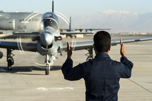 A member of the Afghan air force marshals in an A-29 Super Tucano at Hamid Karzai International Airport, Afghanistan, Jan. 15, 2016. The aircraft will be added to the Afghans' inventory in the spring of 2016. The A-29 Super Tucano is a 'light air support' aircraft capable of conducting close air support, aerial escort, armed overwatch and aerial interdiction. Designed to operate in high temperature and in extremely rugged terrain, the A-29 Super Tucano is highly maneuverable 4th generation weapons system capable of delivering precision guided munitions. It can fly at low speeds and low altitudes, is easy to fly, and provides exceptionally accurate weapons delivery. It is currently in service with 10 different air forces around the world. (U.S. Air Force photo by Tech. Sgt. Nathan Lipscomb)