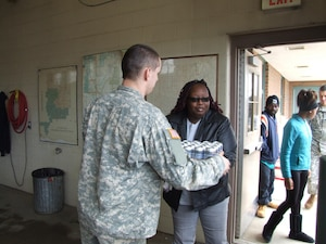 A Michigan National Guard member provides water to a resident of Flint, which is enduring a drinking-water crisis due to lead contamination of the city's water source.