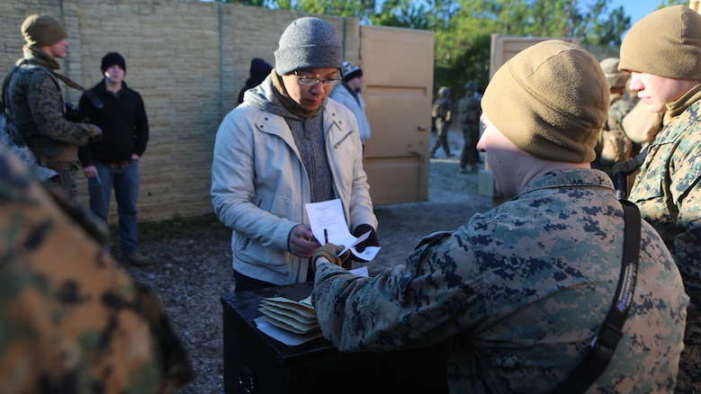 Lance Cpl. Jordan Martin, a rifleman with 2nd Battalion, 2nd Marine Regiment, evaluates and records a refugee role player's identification paperwork during a noncombatant evacuation training operation  at Marine Corps Base Camp Lejeune, North Carolina, Jan. 14, 2016. The Marines successfully processed 28 refugee role players through a notional forward operating base. The exercise was part of the unit's training in preparation for an upcoming deployment to Okinawa, Japan.