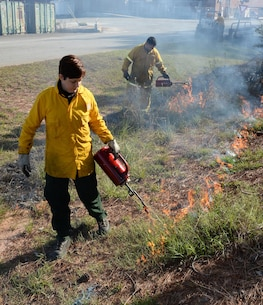 Julie Robbins (front), natural resources manager, and Sgt. Greg Rieder, both with Environmental Branch, Installation and Environment Division, Marine Corps Logistics Base Albany, conducts the installation's annual prescribed burning of base timber, Jan 11.