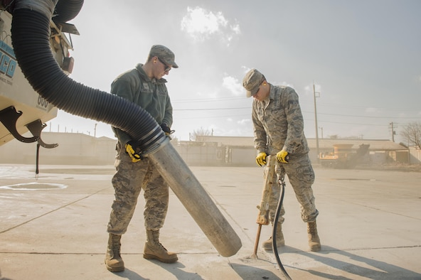 """Airmen 1st Class Jacob Fetters and Brendan Kinser, both 374th Civil Engineer Squadron pavement and equipment technicians, perform a spot repair on a section of Yokota Air Base, Japan, Jan. 13, 2016. From shovels and jackhammers to cranes and bulldozers, the duties of the """"Dirt Boys"""" require them to be experts of a wide assortment of machinery. (U.S. Air Force photo/Airman 1st Class Delano Scott)"""