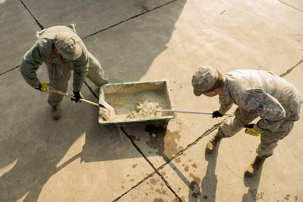 """Senior Airman Tommy Zeus and Airman 1st Class Brendan Kinser, both 374th Civil Engineer Squadron pavements and heavy equipment technicians, prepare to perform a spot repair at Yokota Air Base, Japan, Jan. 13, 2016. As their job requires them to be experts with a wide assortment of machinery, the Airmen referred to as """"Dirt Boys"""" are able to assist other shops and squadrons around base. (U.S. Air Force photo/Airman 1st Class Delano Scott)"""