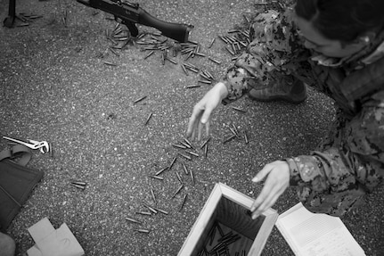 A sailor collects empty shell casings during a weapons sustainment training Jan. 9, 2016 at Joint Base Charleston, S.C .The two day, semi-annual training event was hosted by the Coastal Riverine Squadron 10 Bravo Company, a Navy Reserve team stationed at Joint Base Charleston – Weapons Station. The participants were required to show proficiency and familiarization with the M240B machine gun. (U.S Air Force Photo/Staff Sgt. Jared Trimarchi)