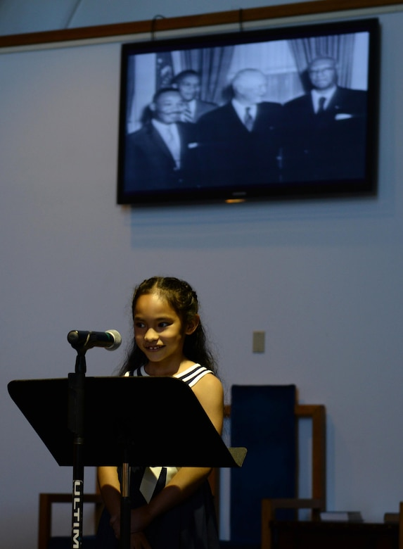 An Andersen Elementary School student reads an essay at the Martin Luther King Jr. Remembrance Ceremony Jan. 14, 2016 at Andersen Air Force Base, Guam. Her essay, about what Martin Luther King Jr. day means to her, was handpicked from all of the submissions turned in by Andersen Elementary students. (U.S. Air Force photo/Airman 1st Class Jacob Skovo)