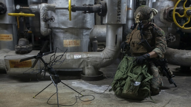 Staff Sgt. Travis Caron sets up satellite communications during a raid Jan. 13, 2015, as part of Realistic Urban Training Exercise on Guam. RUTEX is a high-intensity close-quarter battle training exercise conducted in an actual urban environment to provide a high degree of realism to the training. The exercise is part of the Maritime Raid Force's pre-deployment training before their upcoming deployment with the 31st MEU. Caron, from Sneads Ferry, North Carolina, is the Force Reconnaissance Platoon communications chief with MRF, 31st MEU.