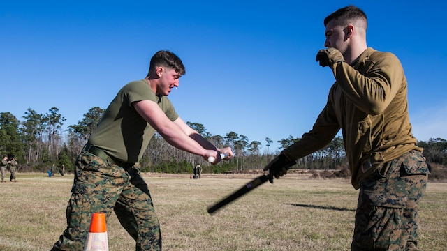 "Lance Cpl. Hunter Rooks, a Marine with Combat Logistics Battalion 22, deflects baton attacks from an assailant after being sprayed with oleoresin capsicum, more commonly known as OC spray, at Camp Lejeune, N.C., Jan. 14. ""The purpose of this course is to gain compliance without using lethal force,"" said Cpl. Hayden Jolly, an artillery section chief with the unit."