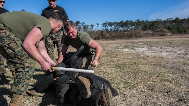 Lance Cpl. Hunter Rooks, left, and Lance Cpl. Joshua Sutton, both Marines with Combat Logistics Battalion 22, perform a two-man takedown against an armed aggressor after being sprayed in the eyes with oleoresin capsicum, more commonly known as OC spray, at Camp Lejeune, N.C., Jan. 14. The take-down was part of an obstacle course, which also entailed the use of other baton techniques, blocking attacks from an assailant and a two-man takedown against an armed aggressor.