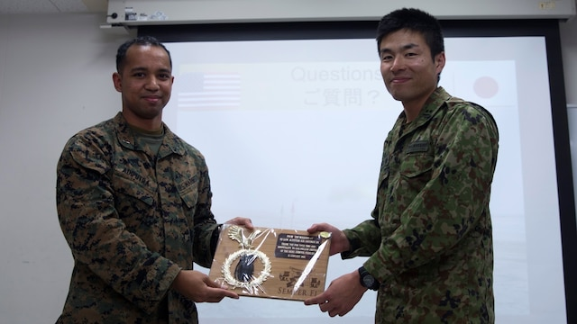 Marine 1st Lt. Yosef E. Adiputra presents a gift to Japan Ground Self-Defense Force 1st Lt. Takahashi during a tour of JGSDF facilities Jan. 13 at Camp Komakado, Shizuoka, Japan. The visit strengthened the relationship between Marines and JGSDF members by allowing the service members to observe each other's training methods and operations. The Marines from 2nd Low Altitude Air Defense Battalion, Marine Aircraft Control Group 28; currently assigned to the 31st Marine Expeditionary Unit, III Marine Expeditionary Force under the unit deployment program, visited their JGSDF counterpart, 1st Anti-Aircraft Battalion, observed weapon systems, tactical vehicles and martial arts demonstrations.