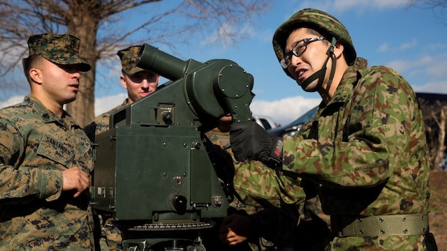 A member of the Japan Ground Self-Defense Force demonstrates the use of a targeting optical aide during a tour of Japan Ground Self-Defense Force facilities Jan. 13 at Camp Komakado, Shizuoka, Japan. The visit strengthened the relationship between Marines and their JGSDF counterpart, 1st Anti-Aircraft Battalion, by allowing them to observe training procedures, weapon systems, tactical vehicles and equipment. The Marines are from 2nd Low Altitude Air Defense Battalion, Marine Aircraft Control Group 28; currently assigned to the 31st Marine Expeditionary Unit, III Marine Expeditionary Force under the unit deployment program.