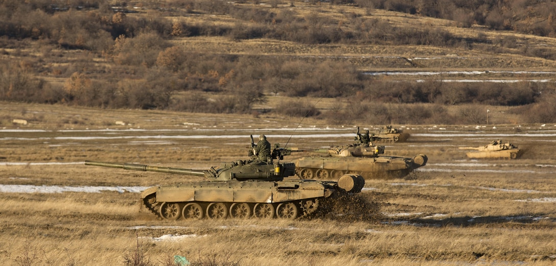 U.S. Marine M1A1 Abrams tanks and Bulgarian T-72 tanks conduct bounding over watch maneuver training during Platinum Lion 16-2 at Novo Selo Training Area, Bulgaria, Jan. 8, 2016. U.S. Marine Corps photo by Cpl. Justin T. Updegraff
