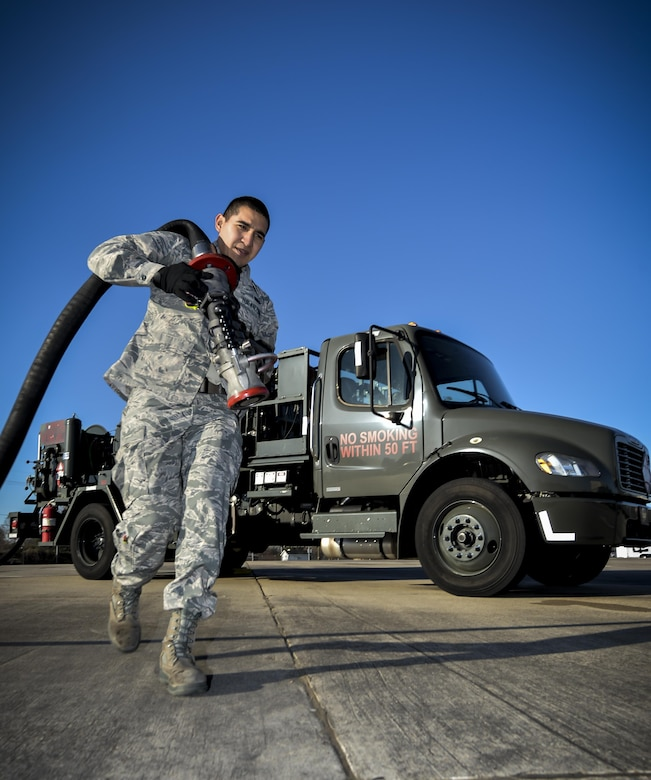 Airman 1st Class Ivan Saldivar, 2nd Logistics Readiness Squadron fuel distribution operator, carries a fuel hose from an R-12 hydrant servicing truck at Barksdale Air Force Base, La., Jan. 11, 2016. This truck fuels aircraft faster than conventional trucks by pumping fuel directly from the underground piping system. (U.S. Air Force photo/Airman 1st Class Mozer O. Da Cunha)