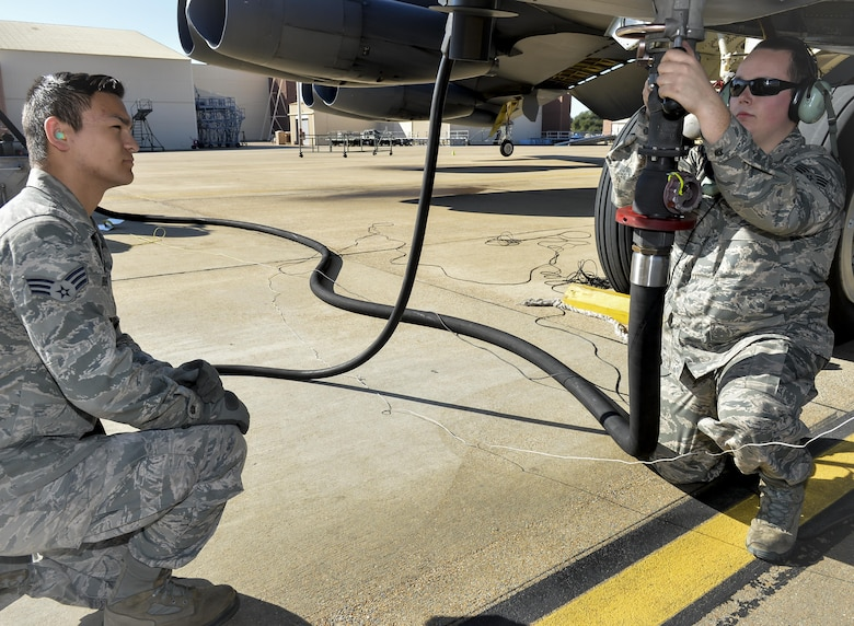 Senior Airman William Burford, 2nd Logistics Readiness Squadron fuel distribution operator, monitors Senior Airman Michael Breiter, 2nd Maintenance Squadron crew chief, as he attaches a fuel nozzle to a B-52 Stratofortress at Barksdale Air Force Base, La., Jan. 12, 2016. The B-52 can hold about 100,000 to 200,000 pounds of fuel per sortie, taking one to two hours to fill the tanks. (U.S. Air Force photo/Airman 1st Class Mozer O. Da Cunha)
