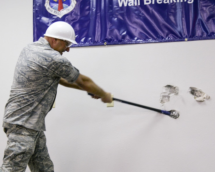 Col. Stephen Kravitsky, 90th Missile Wing commander, takes a sledgehammer to a wall in the 90th Medical Group Medical Treatment Facility during a ceremony Jan. 19, 2015, on F.E. Warren Air Force Base, Wyo. Construction to expand the MTF is scheduled to begin in February, creating a more patient-friendly and efficient atmosphere. (U.S. Air Force photo by Airman 1st Class Malcolm Mayfield)