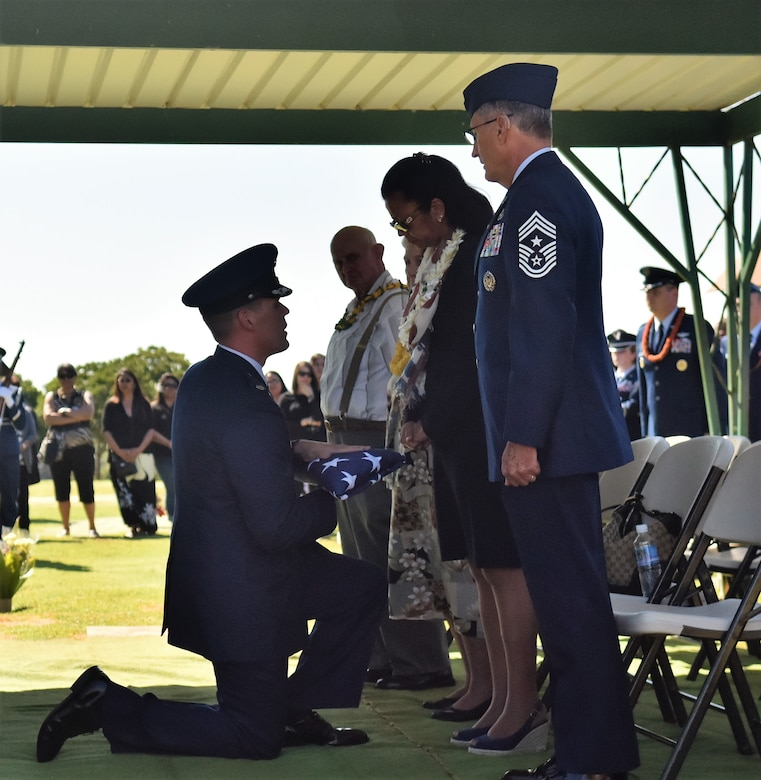 Lieutenant Col. Andrew Campbell, 36th Airlift Squadron commander, presents a folded American flag to Eva Hake during Senior Airman Jeremy M. Jutba-Hake's funeral, Tuesday, Jan. 20, 2016, at Mililani Memorial Park, located in Mililani, Hawaii. (U.S. Air Force photo by Staff Sgt. Christopher Stoltz/Released)