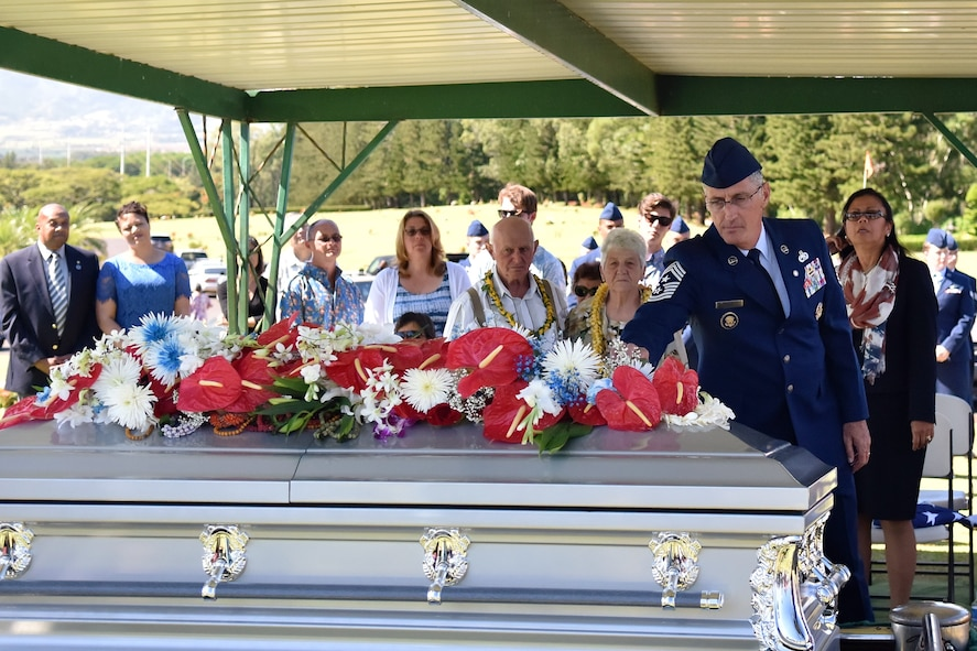 Chief Master Sgt. (Ret.) Jonathan Hake, says a final good bye to his son Senior Airman Jeremy M. Jutba-Hake before he is laid to rest during a memorial service, Tuesday, Jan. 20, 2016, at Mililani Memorial Park, located in Mililani, Hawaii. (U.S. Air Force photo by Staff Sgt. Christopher Stoltz/Released)