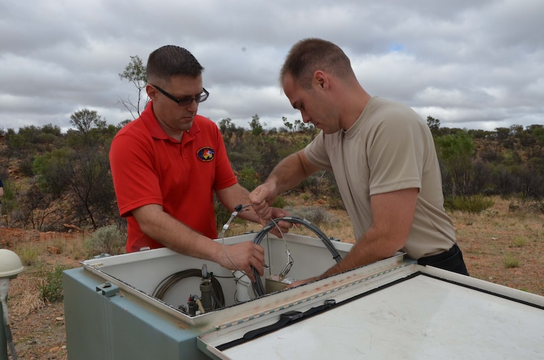Senior Airman Jeremiah H. Odendahl (left) and Staff Sgt. David D. Mose Jr., both seismic technicians at Detachment 421 in Alice Springs, Australia, conduct routine maintenance at one of the detachment's 22 seismic detectors that contribute to the U.S. Atomic Energy Detection System.  The seismic work performed at the detachment is part of the Air Force Technical Applications Center's worldwide mission of nuclear treaty monitoring.  (U.S. Air Force photo by Susan A. Romano)