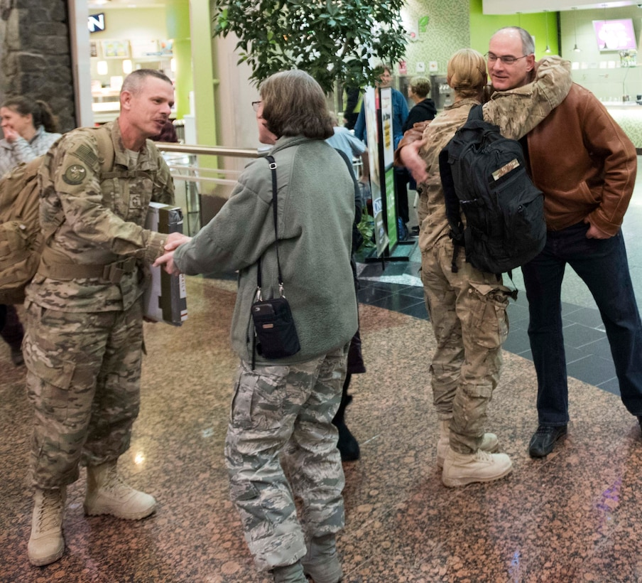 ANCHORAGE, Alaska -- At left, Chief Master Sgt. Keith Wilson, superintendent of the Alaska Air National Guard's 176th Civil Engineer Squadron, gets a welcome-home handshake from Col. Karen Mansfield, commander of the Alaska Air National Guard, at Ted Stevens International Airport here Jan. 13, 2015. At right, Master Sgt. Bonnie Gardino, the 176th CES utilities supervisor, gets a hug from former 176th CES Fire Chief Mark Brauneis. Wilson and Gardino were among several 176th CES members returning from a six-month deployment to Afghanistan. (U.S. Air National Guard photo by Capt. John Callahan/released)
