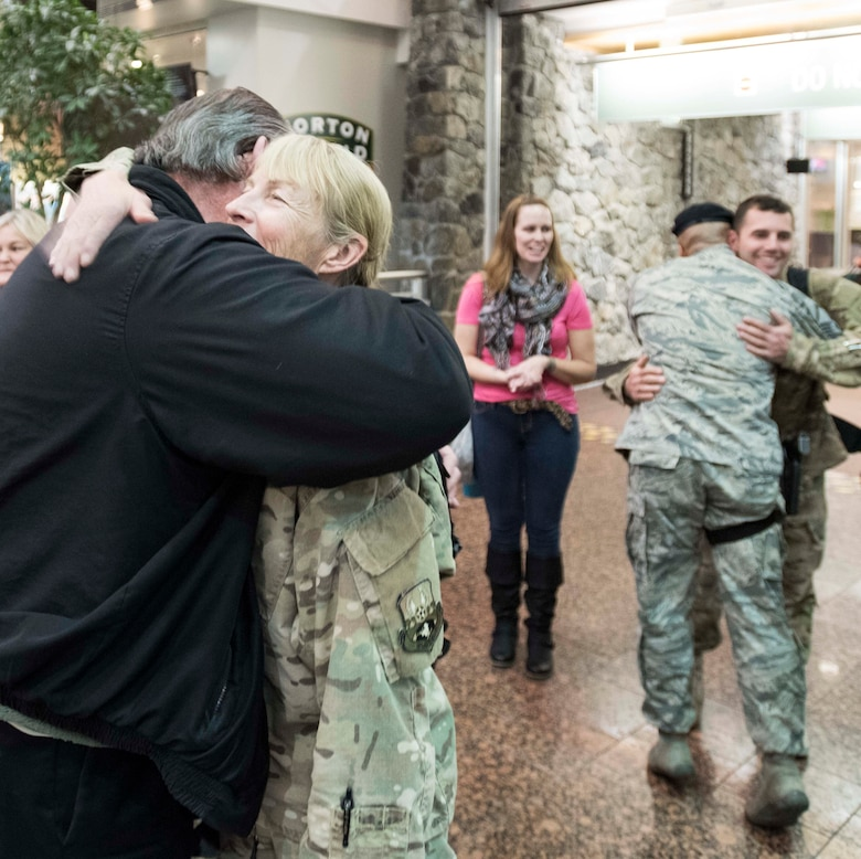 ANCHORAGE, Alaska -- Master Sgt. Bonnie Gardino, utilities supervisor for the Alaska Air National Guard's 176th Civil Engineer Squadron, gets a welcome home hug from former 176th CES member George Waters at the Ted Stevens International Airport here Jan. 13, 2016. Gardino was one of several 176th CES members returning from a six-month deployment in the Middle East. (U.S. Air National Guard photo by Capt. John Callahan/released)