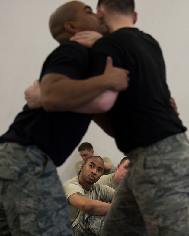 Staff Sgt. Wilbertson Smith, 423rd Security Forces Squadron patrolman from RAF Alconbury, United Kingdom, watches as instructors demonstrate a self-defense maneuver during a Security Forces combative course Jan. 14, 2016, at Ramstein Air Base, Germany. The seven-day course is designed to teach security force members weapon retention and self-defense so they can handle hostile situations by the most peaceful means necessary. Though the course is held at Ramstein, geographically separated units send members to be trained as an instructor and spread that knowledge upon their return to their home station. (U.S. Air Force photo/Senior Airman Jonathan Stefanko)