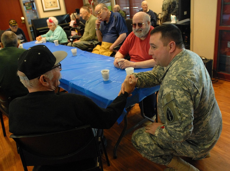 Sgt. Zach Mott, public affairs specialist with the U.S. Army Reserve's 207th Public Affairs Detachment, swaps stories with a U.S. Army veterans during a visit to the Colorado State Veterans Home at Fitzsimmons, Jan. 9. Mott and the other Soldiers of the 207th PAD ate lunch and visited with the veterans who reside in the Veterans Home.
