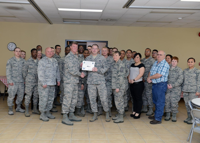 "Tech. Sgt. Zachariah Grooms, center, 47th Communications Squadron NCO in charge of Cyber Systems Operations, accepts the ""XLer of the Week"" award from Col. Thomas Shank, left, 47th Flying Training Wing commander, and Chief Master Sgt. Teresa Clapper, right, 47th FTW command chief, here, Jan. 19, 2016. The XLer is a weekly award chosen by wing leadership and is presented to those who consistently make outstanding contributions to their unit and Laughlin. (U.S. Air Force photo by Senior Airman Jimmie D. Pike)"