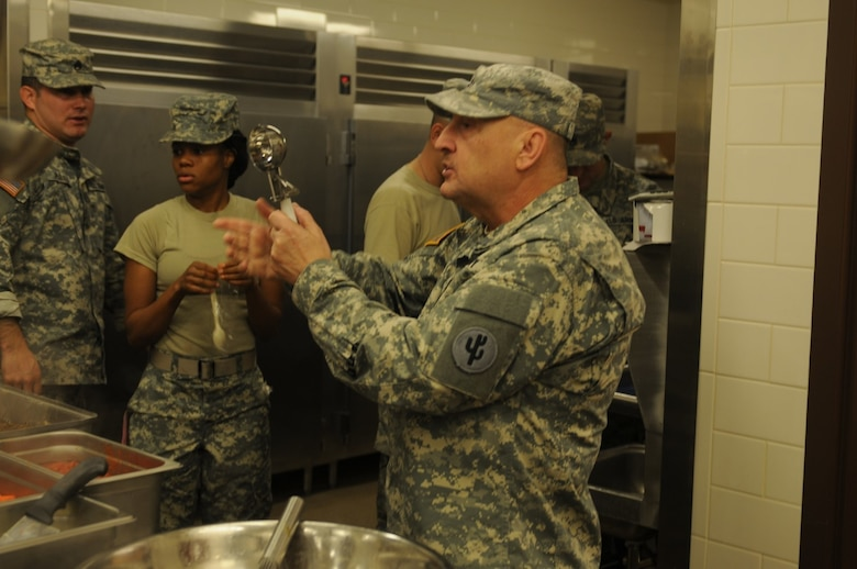 Chief Warrant Officer 2 Danny Wolf, 103rd Sustainment Command (Expeditionary) and Army Reserve Culinary Arts Team coach, demonstrates a cooking technique during a training session in Sloan, Nev.