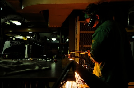 160112-N-PN275-019 DIEGO GARCIA, British Indian Ocean Territory (Jan. 12, 2016) Hull Technician Fireman Thomas Barnett, from USS Emory S. Land (AS 39) weld shop, cuts metal for a navigation chair for guided-missile submarine USS Florida (SSGN 728). Emory S. Land is a forward deployed expeditionary submarine tender on an extended deployment conducting coordinated tended moorings and afloat maintenance in the U.S. 5th and 7th Fleet areas of operations. (U.S. Navy photo by Mass Communication Specialist 3rd Class Zachary A. Kreitzer/Released)