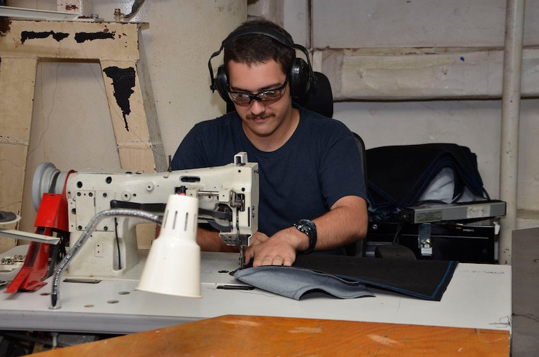 160119-N-VH871-006 DIEGO GARCIA, British Indian Ocean Territory (Jan. 19, 2016) Hull Repair Technician Fireman Zachary James assigned to the submarine tender USS Emory S. Land (AS 39) sews together pieces of Naugahyde to make a seat cover for the guided missile submarine USS Florida (SSGN 728) as part of a continuous maintenance availability. Emory S. Land is a forward deployed expeditionary submarine tender on an extended deployment conducting coordinated tended moorings and afloat maintenance in the U.S. 5th and 7th Fleet areas of operations. (U.S. Navy photo by Mass Communication Specialist 3rd Class Austin L. Ingram/Released)