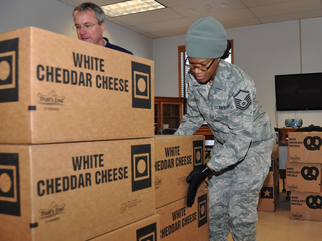 Master Sgt. Savine Marshall, NCO in charge of Airman and Family Readiness, stacks cases of popcorn at the Niagara Falls Air Reserve Station on January 6, 2016. The popcorn was a donation from the Boy Scouts of America of the Greater Niagara Frontier Council. (U.S. Air Force photo by Staff Sgt. Richard Mekkri)
