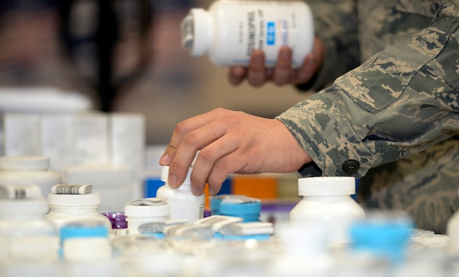 Senior Airman Bruce Coleman, 22nd Medical Support Squadron logistics warehouse technician, places a bottle of pills on a cart in the medical warehouse Jan. 19, 2016, at McConnell Air Force Base, Kan. Once the medicines are organized on the cart, they are delivered to the pharmacy for stock. (U.S. Air Force photo/Senior Airman Colby L. Hardin)