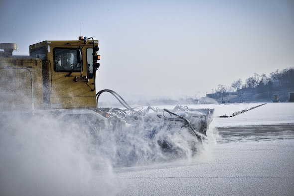 An Airman from the 51st Civil Engineer Squadron uses a runway sweeper truck to remove the first snow of the year on the flightline behind the Air Mobility Command passenger terminal Jan. 13, 2016, at Osan Air Base, South Korea. Airmen remove snow from the runways, taxiways and flightline to ensure passenger and aircraft safety. The runway sweeper head is approximately 20-feet wide, which helps reduce the amount of time it takes to completely clear the flightline of snow. (U.S. Air Force photo/Tech. Sgt. Travis Edwards)
