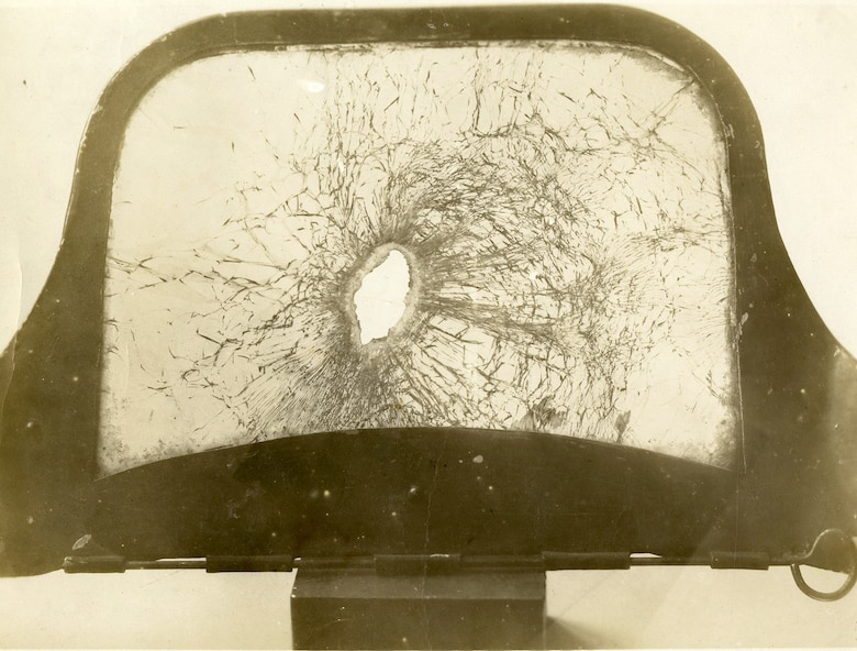 """Casualties among pilots were common during World War I, though miraculously, Private John E. Tynan, a Nieuport pilot, very narrowly managed to avoid his own brush with death. He continued to serve with the 26th Aero Squadron in France until the end of the war. He captioned this photo: """"Bullet hole through windshield of my Nieuport over Chateau Thierry, France, November 1918 -- happily at a 90 degree angle."""" (U.S. Air Force photo)"""