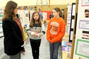Carol Elder, Huntsville Center's Interior Design chief, listens as fifth-graders Kirsten Goodenought and Ashlyn Harris explain how saltwater makes gummy bears shrink during the Challenger Elementary School Science Fair Jan. 20.