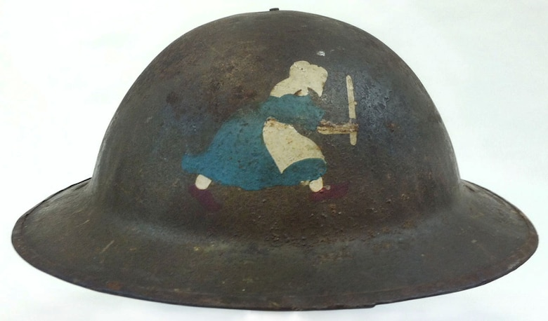 """This helmet was worn during World War I by Lt. Milton K. Lockwood of the 50th Aero Squadron, who piloted DH-4 aircraft and survived three crash landings. The 50th Aero Squadron insignia is the Dutch Girl, the trademark emblem of Old Dutch Cleanser, which was adopted to represent that the squadron's focus was to """"clean up on Germany"""" during WWI. (U.S. Air Force photo)"""