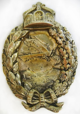 At the outbreak of World War I, LeRoy J. Prinz went to France to train as a pilot. Initially, he served in the French Aviation Corps, then with the 94th Aero Squadron and the 27th Aero Squadron. This aviator pin has a front design of a wreath with bow at bottom and a triptych crown at top. Centered within the wreath opening is a scene of an aircraft flying over mountains, fields and buildings in Europe. The back is engraved: HANS EHL,  SHOT DOWN,  JULY 1 1917,  BY LE ROY PRINZ (U.S. Air Force photo)
