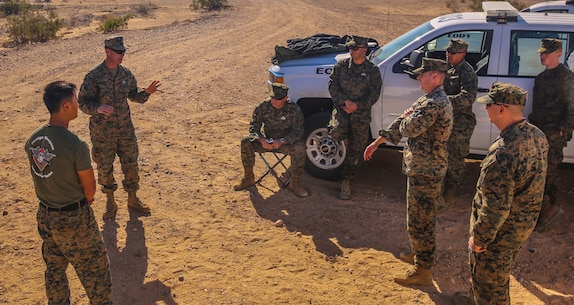 Chief Warrant Officer 3 John Hermann (top left), the officer-in-charge of Headquarters and Headquarter Squadron's explosive ordnance disposal unit, based out of Marine Corps Air Station Yuma, debriefs his Marines after completing a training exercise at the Barry M. Goldwater Range in Yuma, Ariz., Tuesday, Dec. 8, 2015.