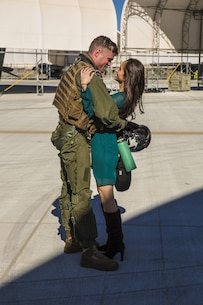 Capt. Phil Smith, an AV-8B Harrier pilot with Marine Attack Squadron 311, based out of Marine Corps Air Station Yuma, reunites with his wife at the VMA-311 hangar aboard MCAS Yuma, Ariz., Saturday, Dec. 11, 2015. VMA -311 was on a six-month deployment in support of the 15th Marine Expeditionary Unit.