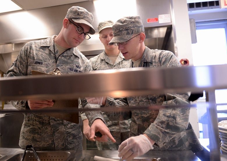 U.S. Air Force Staff Sgt. Daniel Jones, a 509th Force Support Squadron (FSS) in-flight kitchen manager, left, oversees a food temperature-check performed by Senior Airman Justin Stewart, a 509th FSS shift leader at Whiteman Air Force Base, Mo., Jan. 21, 2016. Aside supervising meal-prep, Jones is in charge of the Touch and Go in-flight kitchen's monthly budget and minor repairs on mission-essential equipment. (U.S. Air Force photo by Senior Airman Sandra Marrero)