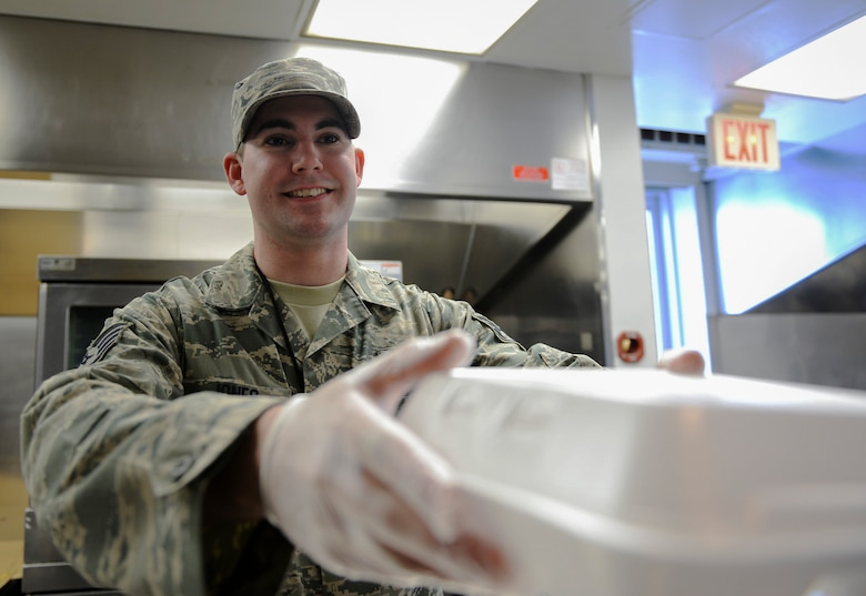 U.S. Air Force Staff Sgt. Daniel Jones, a 509th Force Support Squadron in-flight kitchen manager, hands a meal to a customer at Whiteman Air Force Base, Mo., Jan. 20, 2016. Jones earned the 509th Mission Support Group Supervisor of the Year award through his mentorship and willingness to help his subordinates on and off duty. (U.S. Air Force photo by Senior Airman Sandra Marrero)