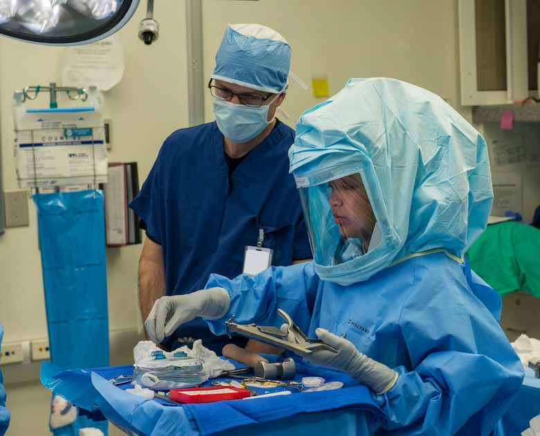 Airman 1st Class Athena Layman, right, 60th Surgical Operations Squadron surgical technician, reaches for a tool Jan. 15, 2016, during a knee replacement surgery at Travis Air Force Base, California, (U.S. Air Force photo by Heide Couch)