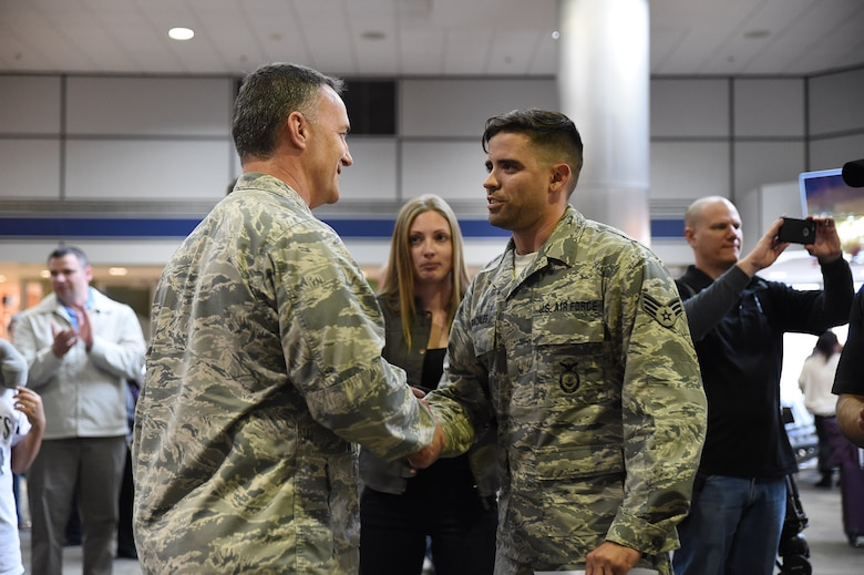 U.S. Air Force Senior Airman Christopher Gonzales, 144th Security Forces Squadron, is welcomed home and promoted to Staff Sgt. by Lt. Col. Dave Johnston, 144th Security Forces Squadron commander, at the Fresno Yosemite International Airport Jan. 21, 2015. Senior Airman Gonzales was deployed for more than seven months in support of Operation Enduring Freedom. (U.S. Air National Guard photo by Senior Master Sgt. Chris Drudge)