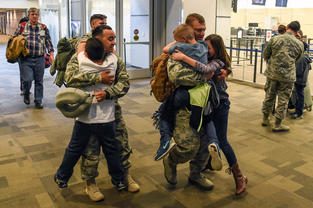 U.S. Air Force Senior Airman Leonardo Perez (left) and Staff Sgt. Kenny Smith (right), both from the 144th Security Forces Squadron, are eagerly greeted by their children at the Fresno Yosemite International Airport Jan. 21, 2015. The 144th Fighter Wing Airmen from Fresno, California were deployed for more than seven months in support of Operation Enduring Freedom. (U.S. Air National Guard photo by Senior Master Sgt. Chris Drudge)