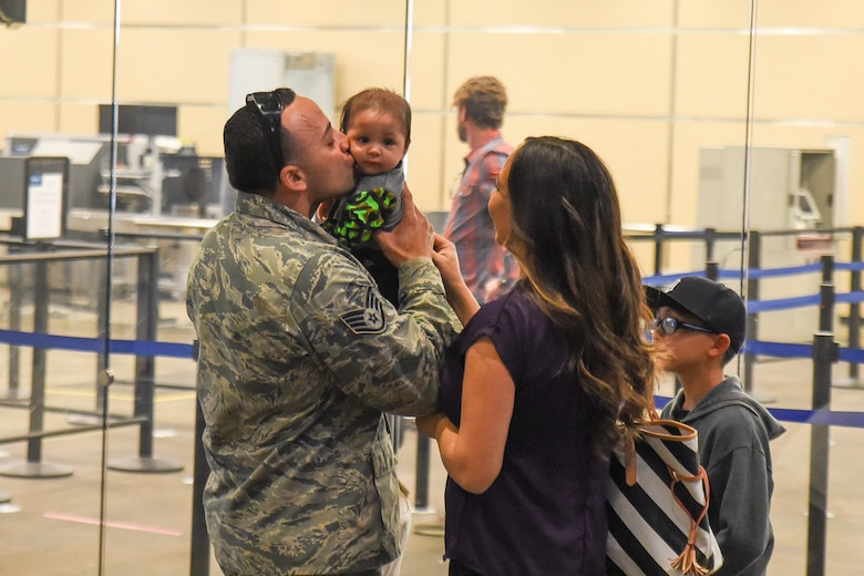 U.S. Air Force Staff Sgt. Roberto Sanchez, 144th Security Forces Squadron, meets his son for the first time upon his return from deployment in support of Operation Enduring Freedom. Staff Sgt. Sanchez and several other Airmen were deployed for more than seven months and were greeted by friends and family at the Fresno Yosemite International Airport Jan. 21, 2015. (U.S. Air National Guard photo by Senior Master Sgt. Chris Drudge)
