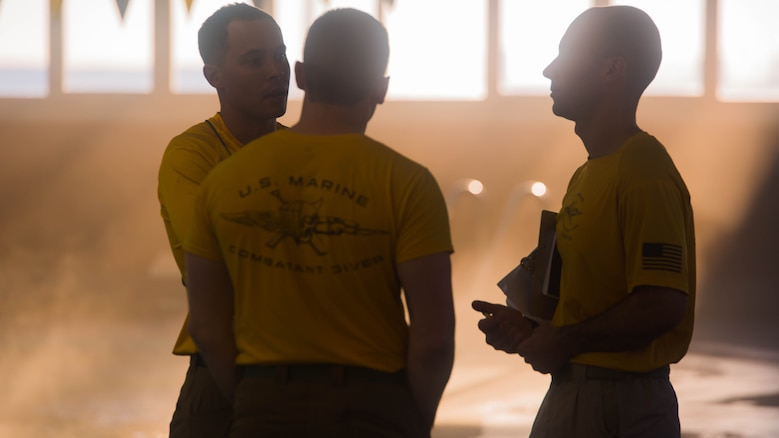 Marine combatant diver instructors discuss the students' performance after a full day of training at Camp Lejeune, N.C., Jan. 19, 2016. The course certifies Marines as dive supervisors whose mission is to oversee dives and ensure that operations are conducted safely and effectively.