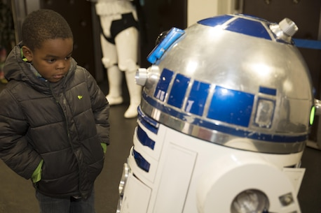 A station resident observes R2-D2 at the Sakura Theater during a promotion for Star Wars: The Force Awakens at Marine Corps Air Station Iwakuni, Japan, Jan. 17, 2016. R2-D2 and a stormtrooper also visited the Crossroads Mall and Marine Corps Exchange Jan. 15. The promotion provided station residents the opportunity to interact and take group photos with both characters.
